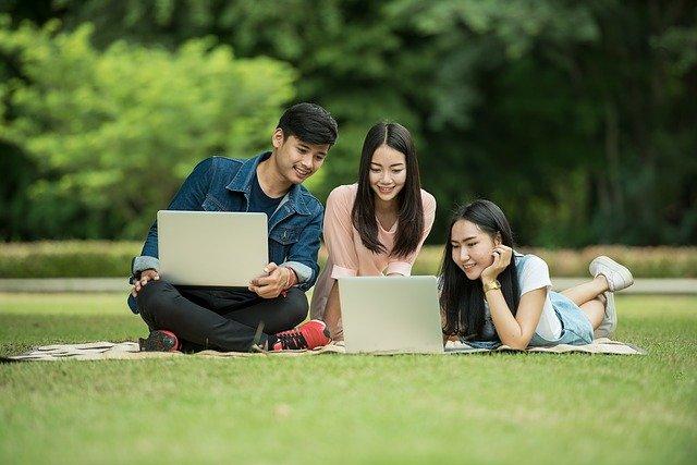 Grupa trojga osób siedzi, leży na zielonej łące. Pracują na laptopach w parku.
